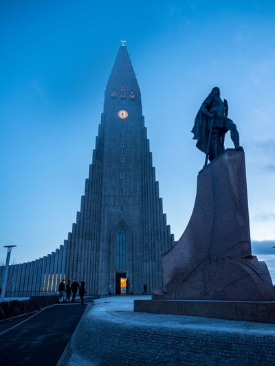 Low Angle View Of Statue And Hallgrimskirkja Against Blue Sky