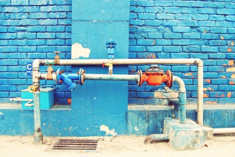 Metal Pipeline Against Brick Wall