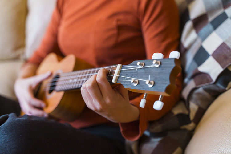 Midsection of woman playing ukulele at home