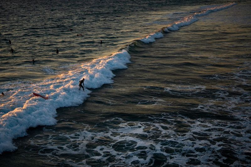 High angle view of man surfing on waves rushing towards shore
