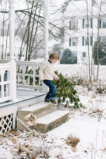 Full length of boy holding snow covered tree during winter