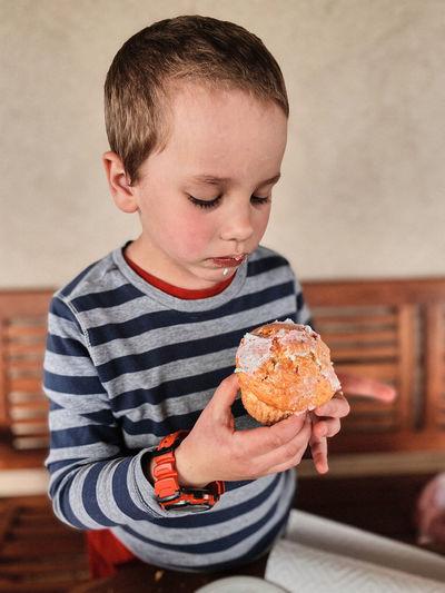 Cute boy eating eating cupcake at home