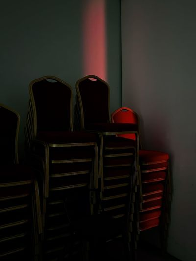 Stack of empty chairs against wall at home