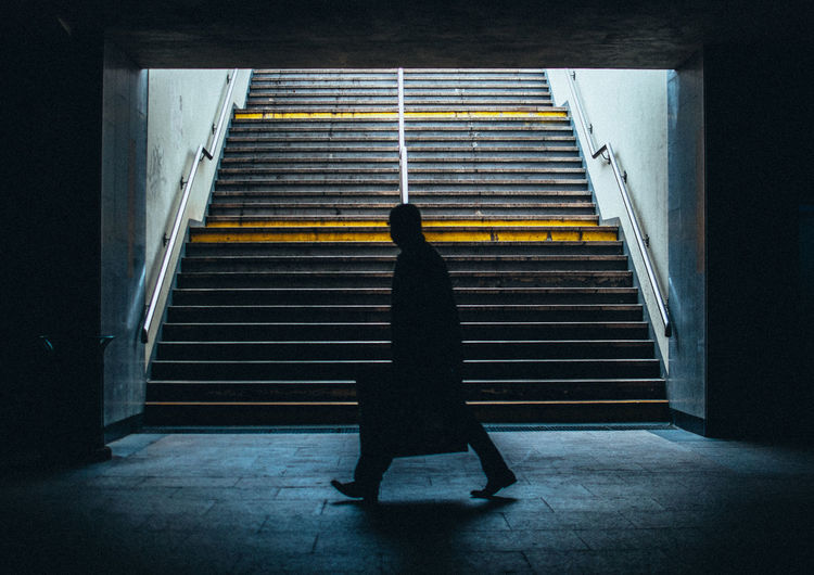 Side View Of A Silhouette Man Walking In Subway