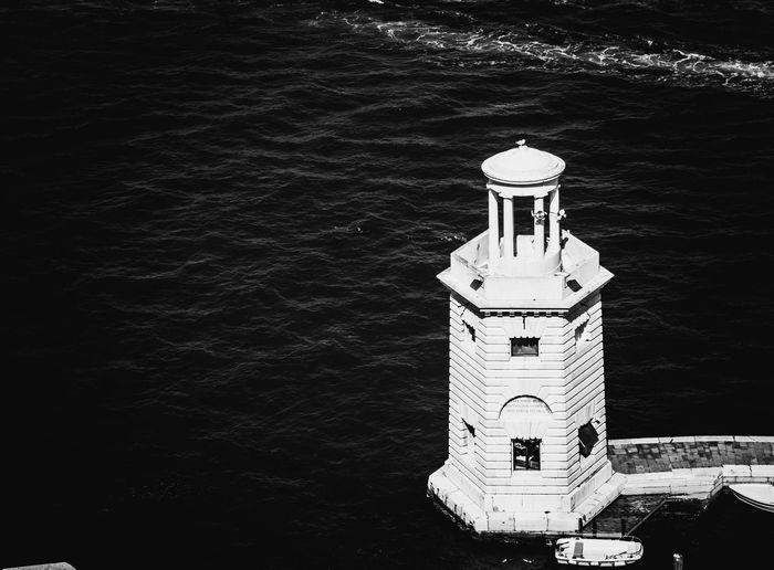 High angle view of lighthouse by sea against building
