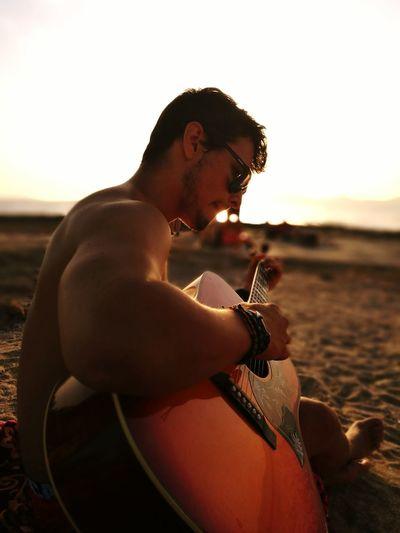 Young Man Playing Guitar At Beach