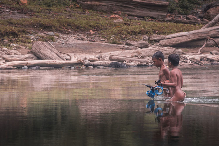 Naked boys fishing in lake