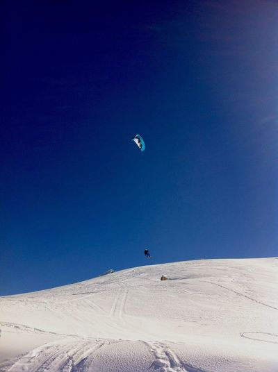 Paraglider Over Snowcapped Mountain