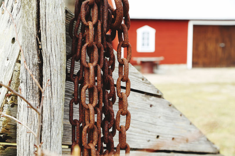 Close-up of rusty metal chain against wooden fence