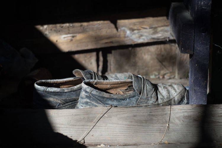 Shoe Indoors  Wood - Material No People Flooring Clothing Table Textile Absence Old Boot Abandoned Day Sunlight Nature Selective Focus Leather Pair