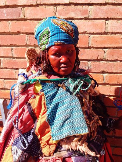 Portrait of tribal woman against brick wall