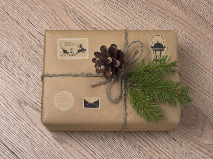 Christmas or New Year gift boxes wrapped in kraft paper with fir branch on wooden background. White; Gift; Christmas; Box; Package; Wrapped; Kraft; Branch; Fir; Needle; Spruce; Background; Brown; Xmas; Decorative; Ball; Spruce; Parcel; Present; Delivery; Packaging; Rope; Decoration; Label; Celebration; Craft; Ribbon; Holiday; Handmade; Cardboard;  Wood - Material Celebration Indoors  High Angle View No People Decoration Table Still Life Close-up Plant Holiday Nature Christmas Brown Directly Above Box Green Color Christmas Decoration Event