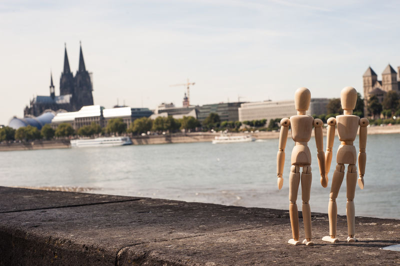 Wooden figurines on retaining wall by rhine river against cologne cathedral in city