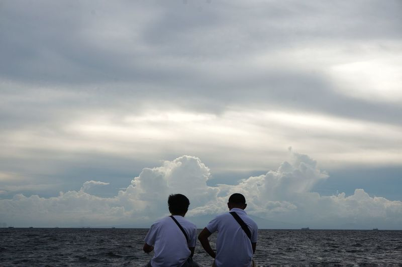 Rear View Of Male Friends Sitting Bay Against Cloudy Sky
