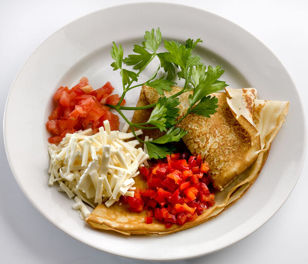 Close-up of pancake with cheese and vegetable served on table