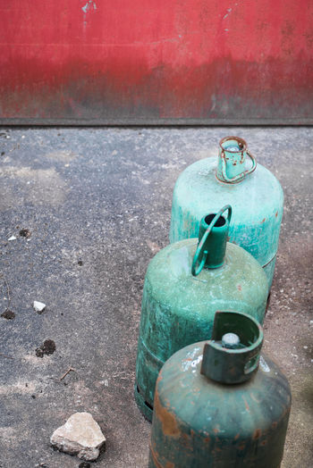 Fossil Gas Cylinder Green Color Red Blue Close-up Concrete Container Cylinder Day Energy Factory Fossil Fuel Group Of Objects High Angle View Metal No People Old Outdoors Rusty Still Life Three Objects Wall - Building Feature Peeling Off Bolt Weathered Run-down Valve Concrete Wall Cement