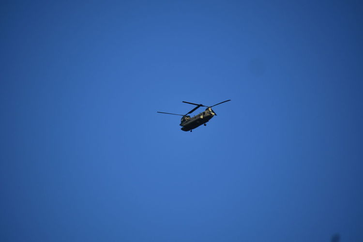 Low Angle View Of Military Helicopter Flying Against Clear Blue Sky