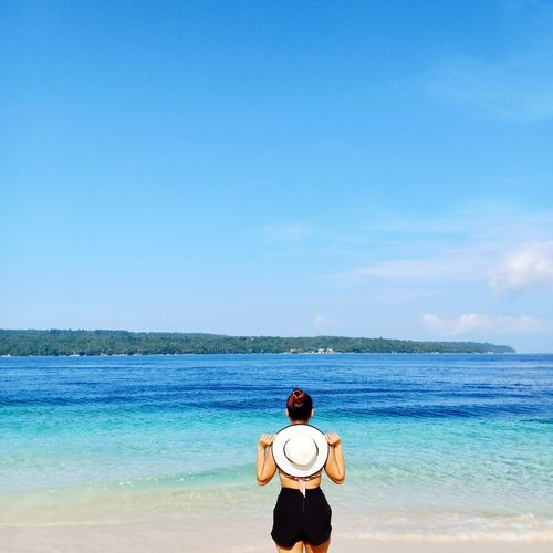 Rear view of woman standing at beach against sky