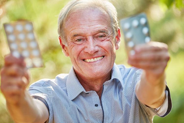 Portrait Of Smiling Man Holding Blister Packs