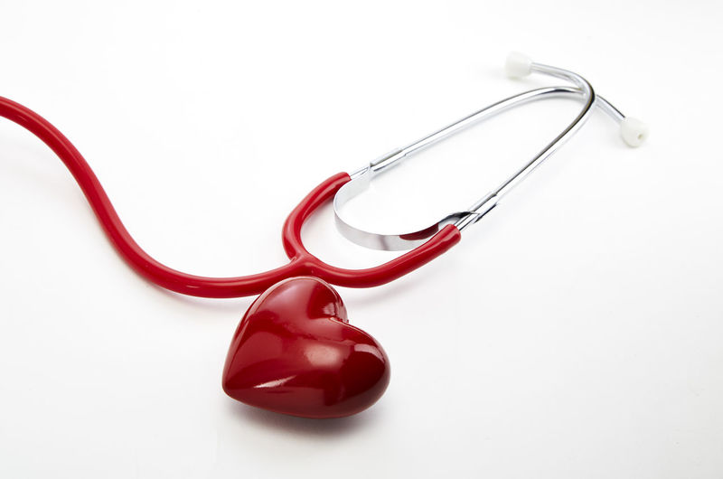 Close-up of red stethoscope with heart shape over white background