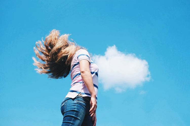 Low Angle View Of Woman Tossing Hair Against Blue Sky On Sunny Day