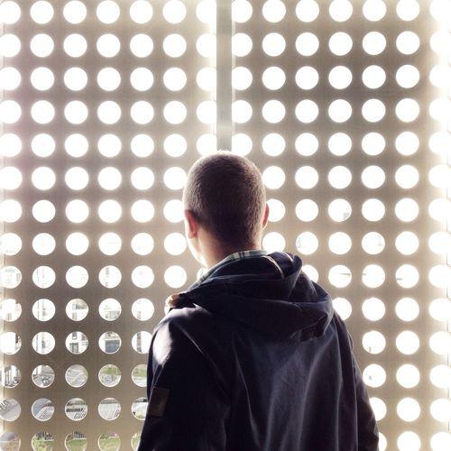 Rear view of man looking through metal grate