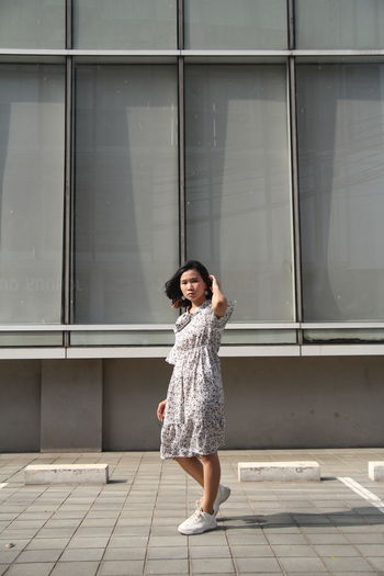 Full length portrait of woman standing against building on footpath