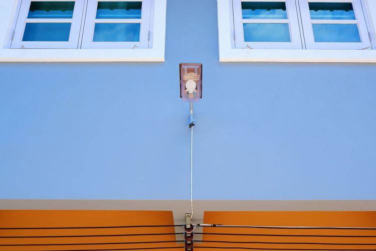 Low angle view of wall mounted street lamp and cable lines with white windows on blue and orange painted wall background, home exterior decoration concept Blue Mounted Street Lamp White Painted Cable Lines Electric Rectangle Pattern Shaped Pipe Street Light Home Exterior Decoration Outside Wall Window Orange Glass - Material Frame Reflection Electrical Equipment EyeEm Selects Architecture Building Geometric Shape Architectural Detail