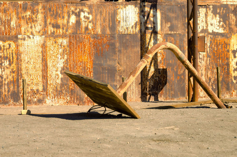 Close-Up Of Fallen Basketball Hoop Against Rusty Corrugated Iron Outdoors