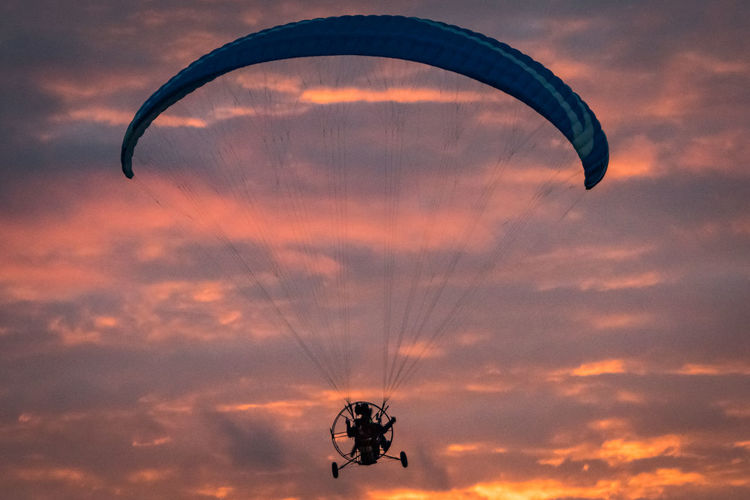 Low angle view of person paragliding against sky during sunset