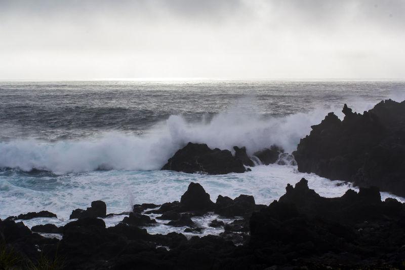 Waves crashing against black volcanic rock formations