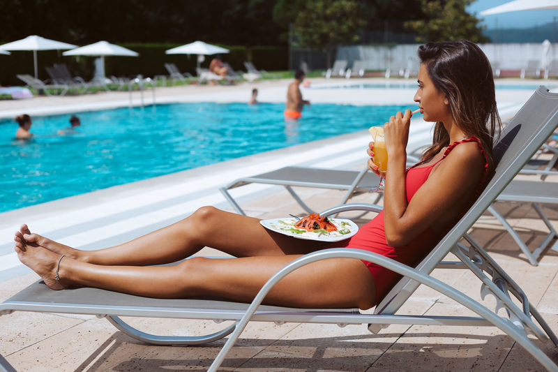 Woman sitting on chair at swimming pool