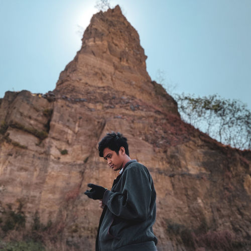Side view of young man standing against rock formation and sky