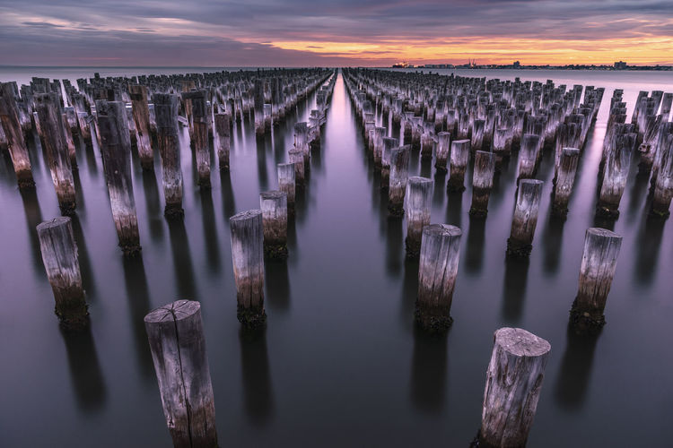 Panoramic shot of wooden posts in sea against sky