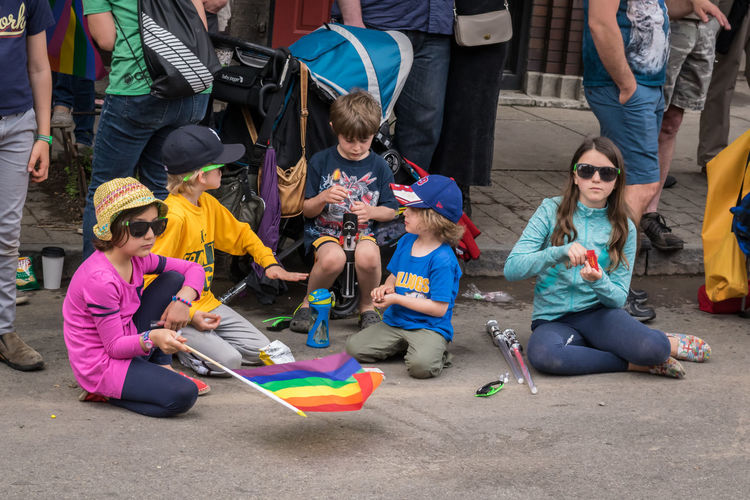 Group of kids sitting on the curb entertaining themselves during the Pride Parade in Buffalo, NY Celebration Rainbow Flags The Street Photographer - 2018 EyeEm Awards Toys Bored Boys Casual Clothing Child Childhood Entertaining Themselves Front View Girls Group Of Kids Group Of People Leisure Activity Lifestyles People Playing Pride Parade Pride Parade 2017 Real People Sitting Sitting On The Street Sunglasses Togetherness