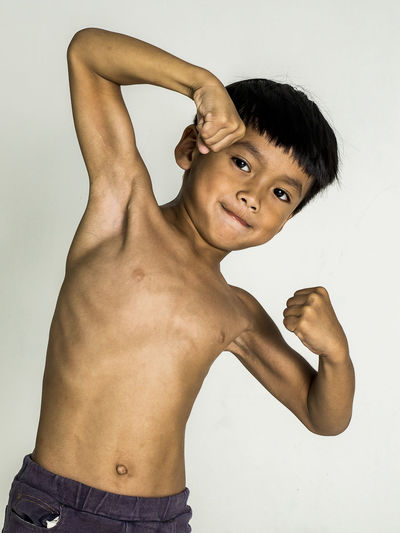 the Boy showing muscle For strong health. The concept of good health Portrait Muscular Build Lifestyles Human Arm Arms Raised Masculinity Bicep Shirtless Healthy Eating Boy