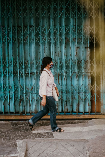 Side view of woman looking away while standing on footpath