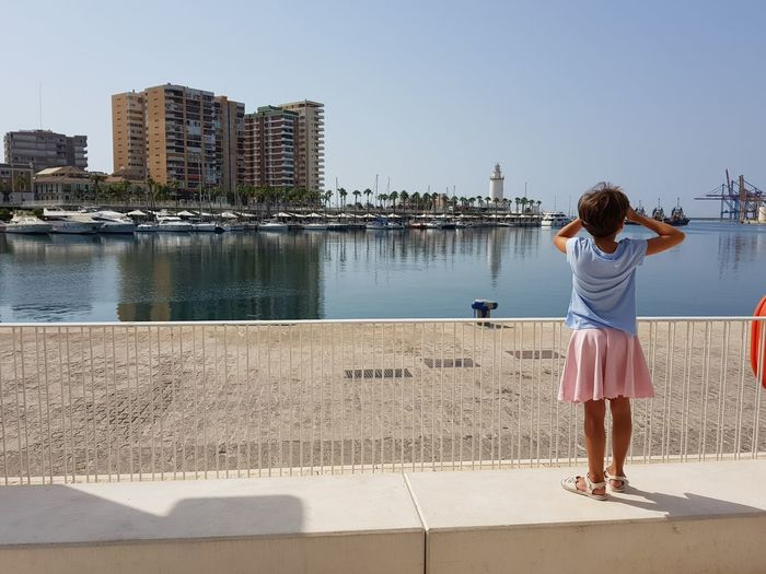 Little girl looking at the Port of Malaga in Andalusia, Spain. Travel Architecture Building Exterior Built Structure Casual Clothing City Cityscape Day Leisure Activity Lifestyles Little Girl Looking At View One Person Outdoors Real People Rear View Sky Skyscraper Standing Sunlight Tourism Travel Destinations Water