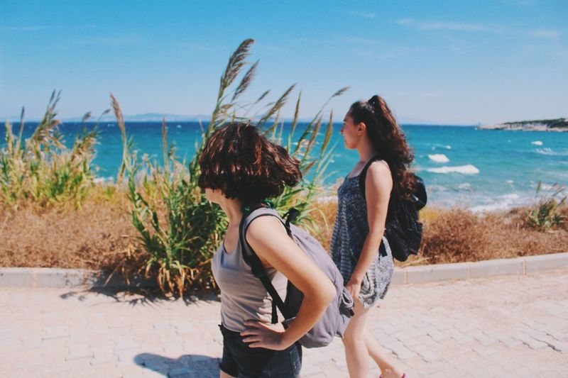 Young women walking on promenade against sky