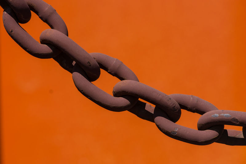 Close-Up Of Metal Chain Against Orange Background