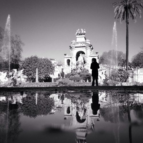 Silhouette Of Woman Looking At Fountain