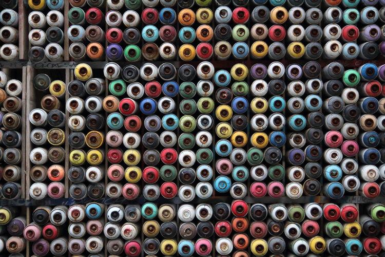 Full frame shot of multi colored aerosol cans