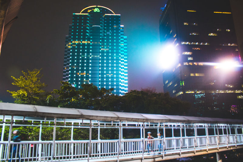 Low angle view of illuminated bridge against buildings at night