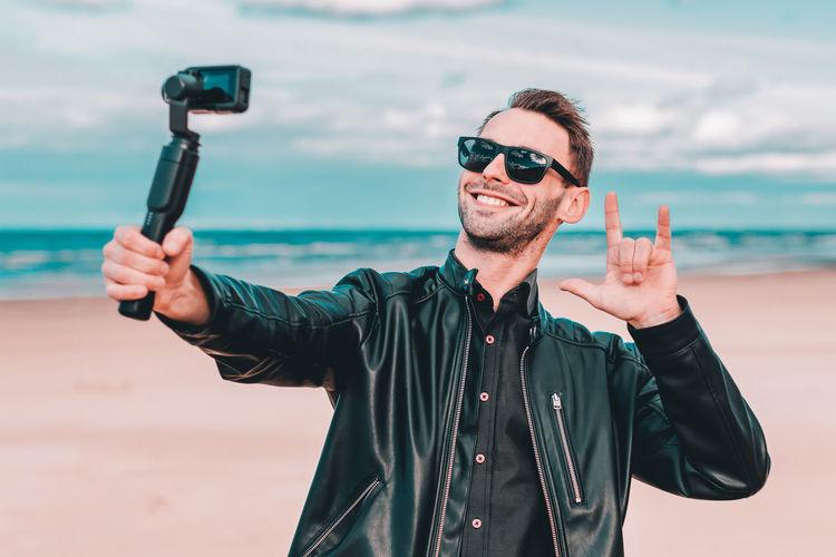 Smiling man filming video camera at beach