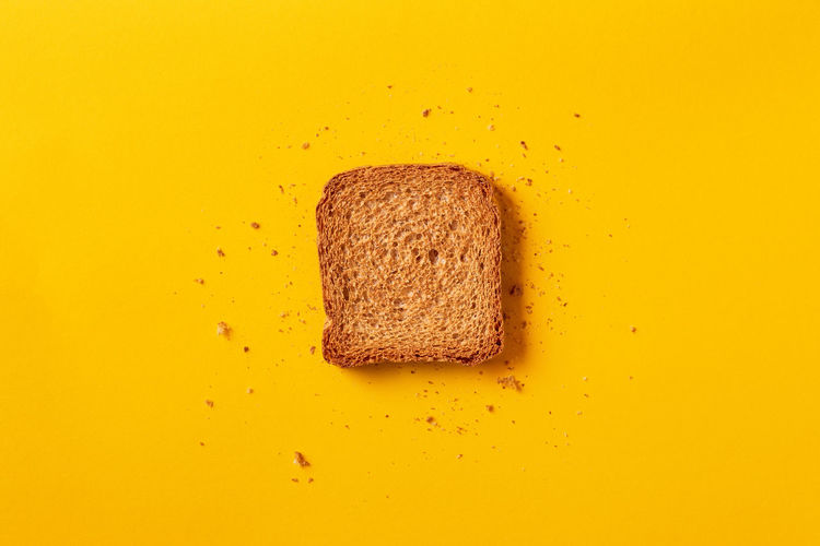 Directly above shot of bread on yellow background