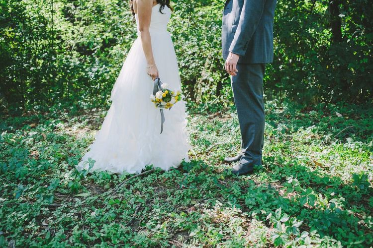 Low Section Of Couple Standing On Field During Wedding
