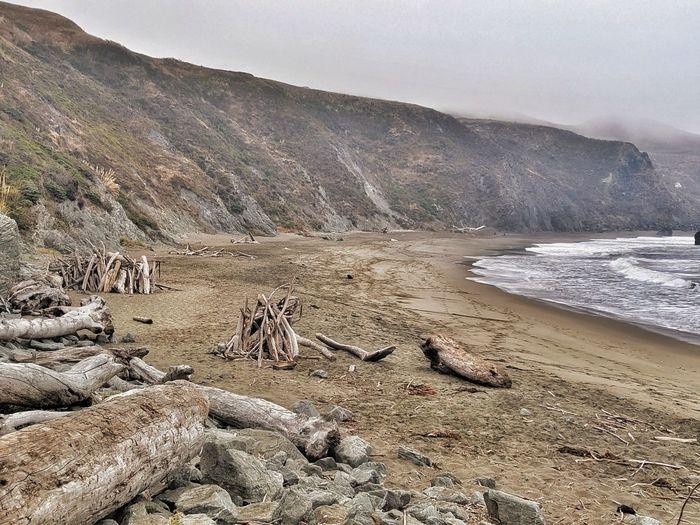 Driftwood houses on ocean beach against cliffs and fog.
