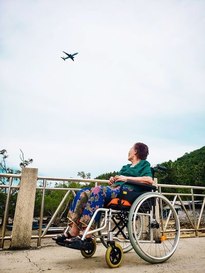 Woman sitting on wheelchair against airplane in sky