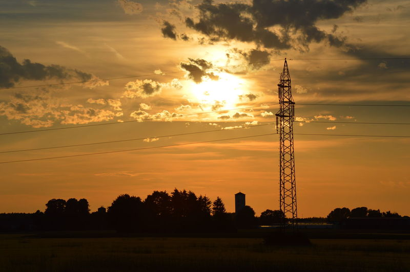 Electricity Pylon On Landscape Against Sunset