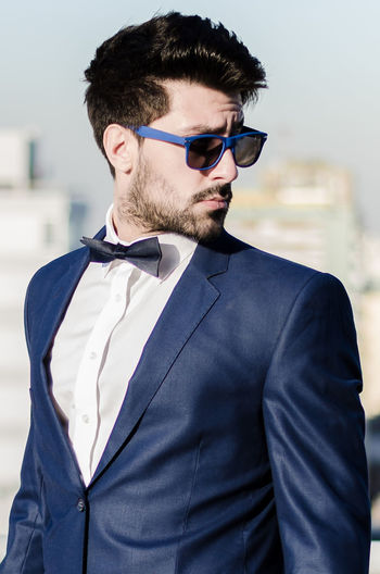 Young man wearing suit and sunglasses standing against sky